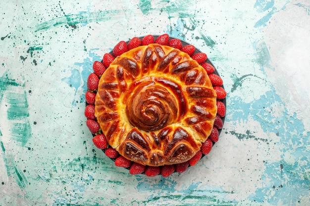 Vista dall'alto rotonda deliziosa torta con fragole rosse fresche su superficie azzurra