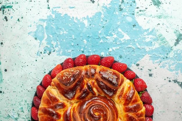 Вид сверху круглый вкусный пирог со свежей красной клубникой на синей поверхности