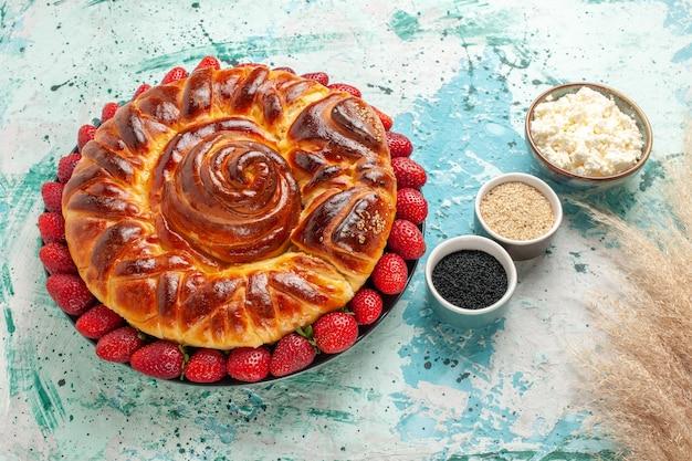 Vista dall'alto rotonda deliziosa torta con fragole fresche sulla superficie blu