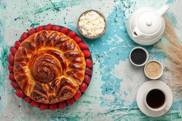 Vista dall'alto rotonda deliziosa torta con fragole fresche sulla superficie azzurra