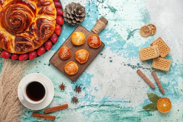 Vista dall'alto rotonda deliziosa torta con cialde di fragole e tazza di tè sulla superficie azzurra