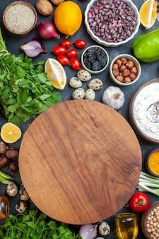 테이블에 있는 그릇 마늘 레몬 토마토 헤이즐넛에 있는 둥근 반죽 보드 콩
