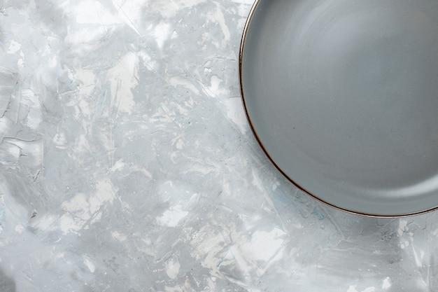 Vista dall'alto piatto rotondo vuoto di colore grigio sulla luce scrivania piatto colore foto posate cucina cibo
