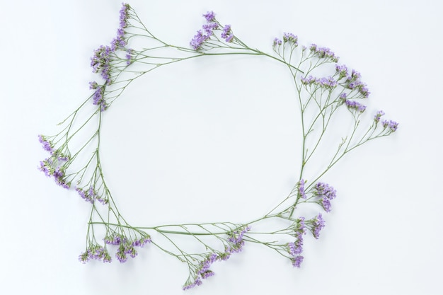 Top view of round flower frame with violet flowers and copy space isolated on white background, flat lay. greeting card concept
