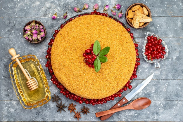 A top view round honey cake delicious and baked with red cranberries honey nuts on the grey desk cake biscuit sugar  photo
