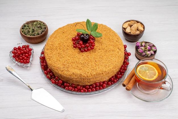 Una torta di miele rotonda con vista dall'alto deliziosa e al forno con mirtilli rossi e tè sulla foto grigia dello zucchero del biscotto della torta della scrivania