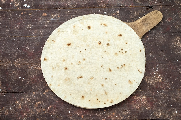 Вид сверху круглый хлеб из лаваша, как на коричневом деревянном столе, тесто для еды, теста