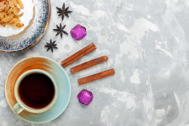 Vista dall'alto torta di zucchero tondo in polvere con tè all'uvetta e caramelle sulla superficie bianca