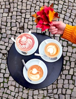 Top view on round metal table outdoors with two cups of latte and cup of hot chocolate. street with cobblestones and hand in saffron yellow sweater holding red maple leaves.