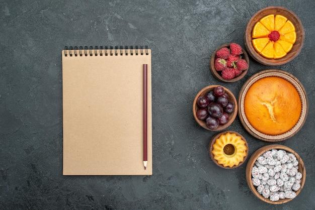 暗い表面の甘い果物のパイケーキに果物とキャンディーの上面図丸いパイ
