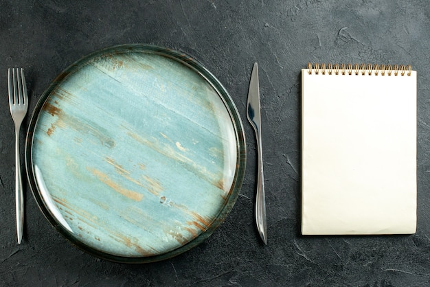 Вид сверху круглое блюдо, обеденный нож и блокнот с вилкой на черном столе