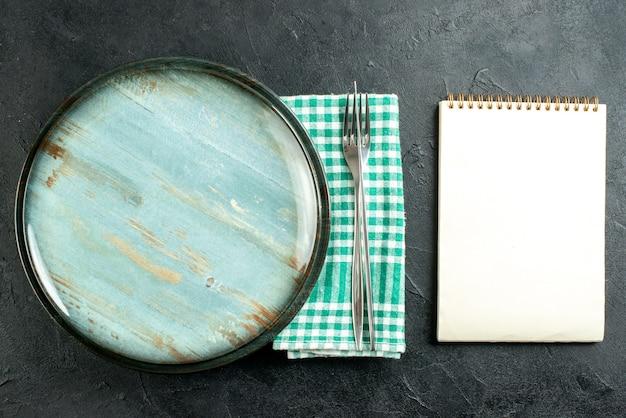Вид сверху круглое блюдо, обеденный нож и вилка на зеленой и белой клетчатой салфетке, блокнот на черном столе