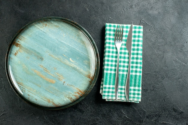 黒のテーブルの空きスペースに緑と白の市松模様のナプキンの上面図ラウンドプラッターディナーナイフとフォーク