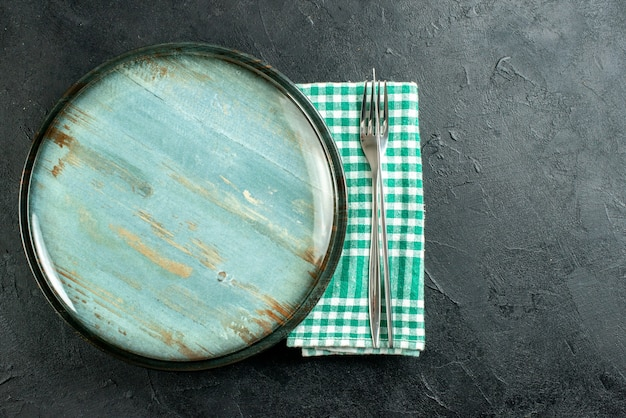 Top view round platter dinner knife and fork on green and white checkered napkin on black surface free space