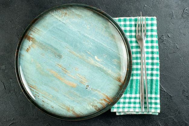 Top view round platter dinner knife and fork on green and white checkered napkin on black surface