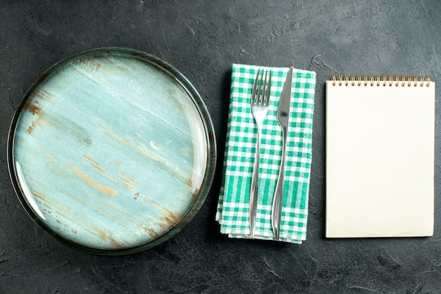 Top view round platter dinner knife and fork on green and white checkered napkin notebook on black table