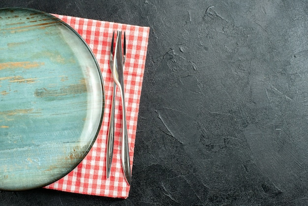 Top view round platter dinner knife and fork on red and white checkered napkin on black table free space