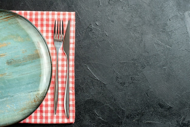 Top view round platter dinner knife and fork on red and white checkered napkin on black table with free space