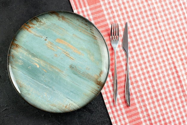 Top view round platter dinner knife and fork on red white checkered tablecloth on black table