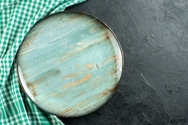 上面図丸い大皿緑と白のテーブルクロス、黒いテーブルの空きスペース
