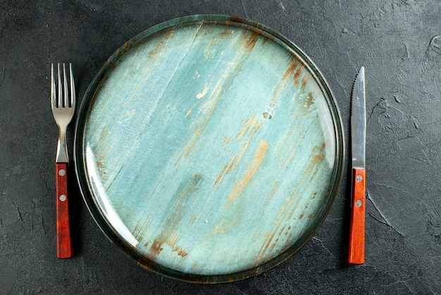 Vista dall'alto coltello piatto rotondo e una forchetta sulla superficie scura