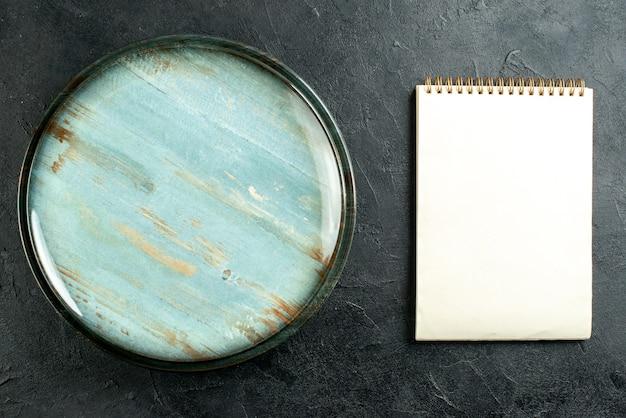 Vista dall'alto taccuino piatto rotondo sulla foto stock tavolo nero