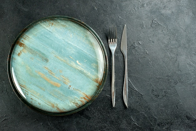 Top view round platter steel fork and dinner knife on black table free place