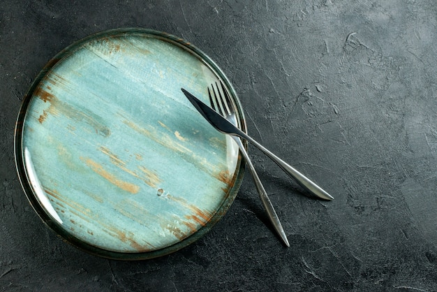 Top view round platter steel fork and dinner knife on black table with free place