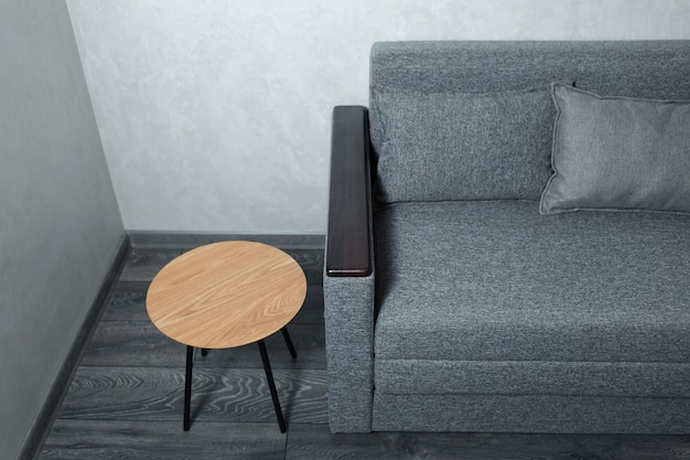 Top view of round small wooden table and gray sofa, on grey laminate floor with textured wall.