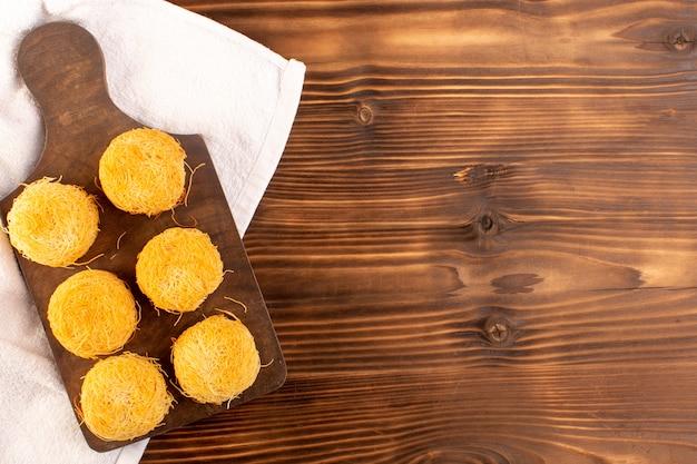 Una vista dall'alto torte dolci deliziosi gustosi dolci isolati allineati sulla scrivania in legno marrone rustico e sfondo marrone zucchero dolce biscotto