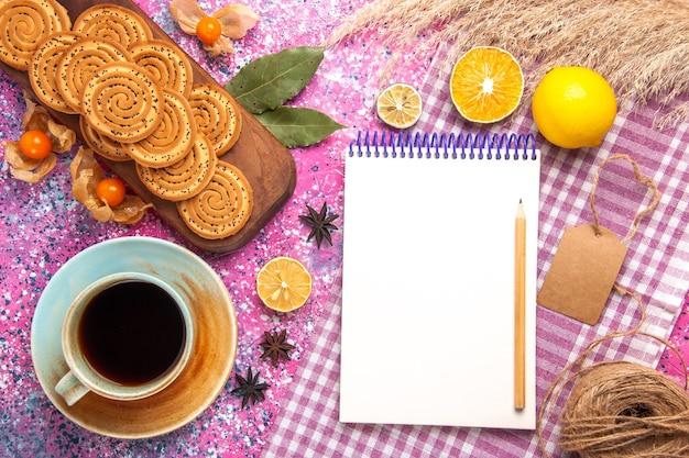 Vista dall'alto di biscotti dolci rotondi con una tazza di tè e limone sulla superficie rosa