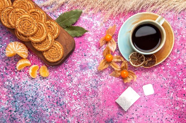 Vista dall'alto di biscotti dolci rotondi con una tazza di tè e mandarini sulla superficie rosa