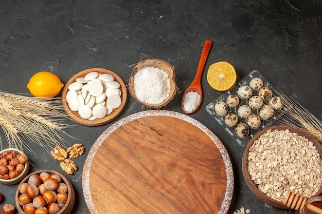 탑 뷰 라운드 우드 보드 레몬 화이트 초콜릿 라운드 코코넛 가루 귀리 헤이즐넛 그릇에 메추리알 테이블에 비올