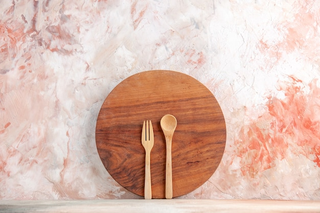 Top view of round wooden chopping board and spoons standing on colorful wall