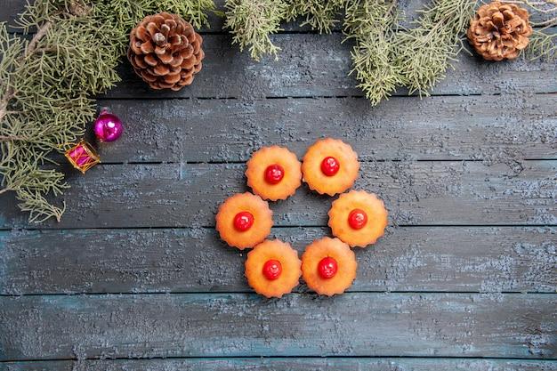 Вид сверху округлые вишневые кексы еловые ветки елочные игрушки и сосновые шишки на темной деревянной земле с копией пространства