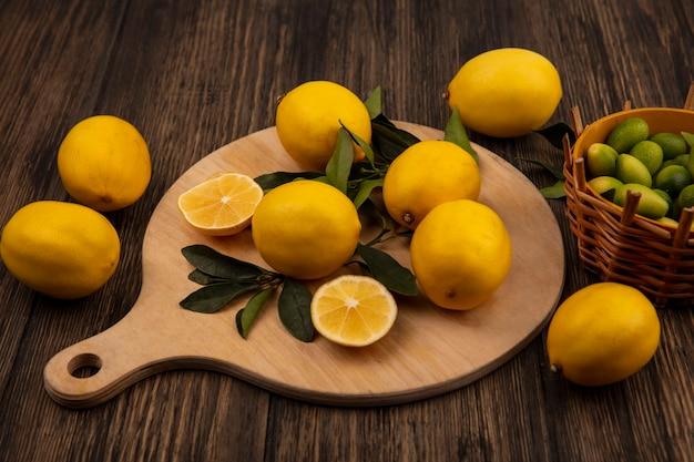 Vista dall'alto di limoni di forma arrotondata isolati su una tavola da cucina in legno con kinkans su un secchio su uno sfondo di legno