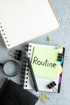 Vista dall'alto routine nota scritta su adesivo verde con blocco note e penna su sfondo bianco colore di lavoro college business school office