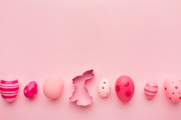 Top view of row of colorful easter eggs with bunny and copy space