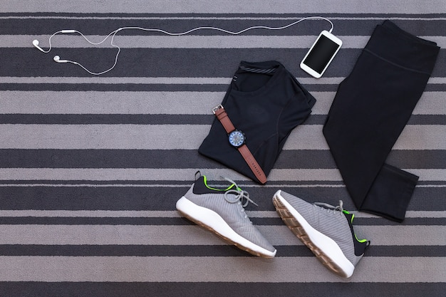 Top view of running shoes, womens clothes, pants tights, smartphone run application on gre