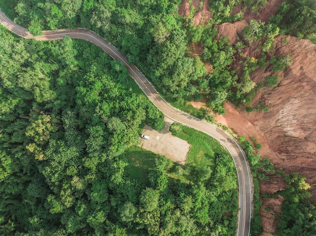 Top view of rural road, path through the green forest and countryside of thailand,