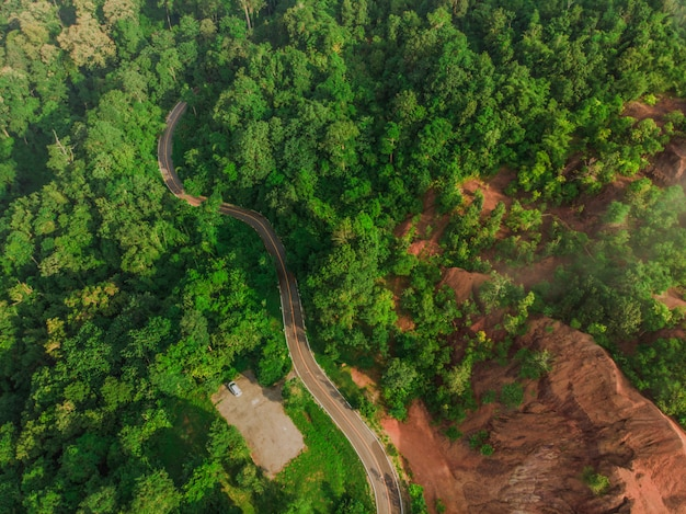 Top view of rural road, path through the green forest and countryside of thailand