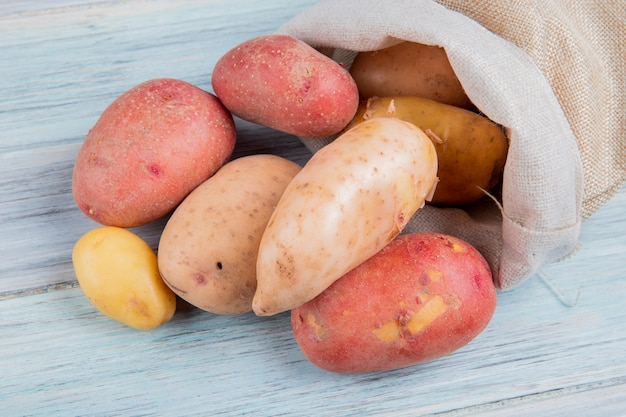 Top view of russet new and red potatoes spilling out of sack on wooden surface