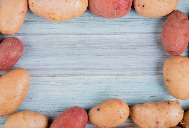Top view of russet and red potatoes set in square shape on wooden surface with copy space
