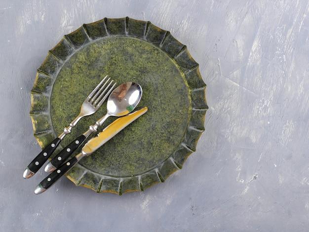 フードフォトグラフィー小道具用の素朴なプレート、スプーン、フォーク、ナイフの上面図