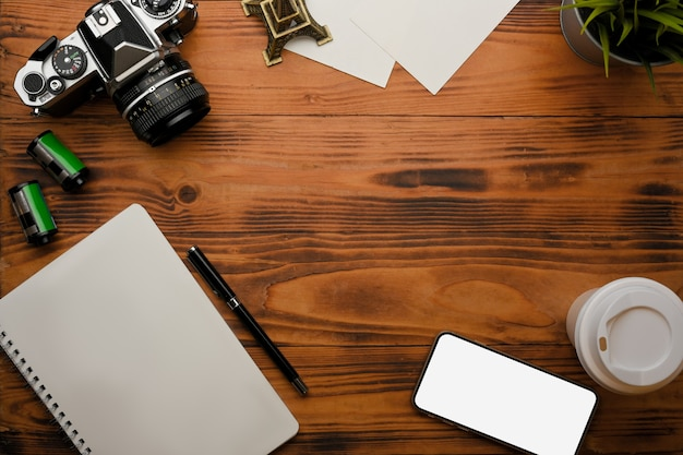 Top view of rustic table with smartphone stationery camera supplies and copy space