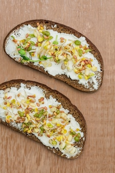 Top view of rye bread sandwiches with cream cheese and sprouted mung beans
