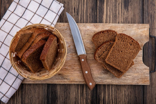 Top view of rye bread slices in basket and on cutting board with knife on plaid cloth on wooden background