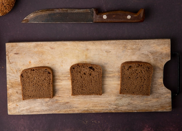 Top view of rye bread slices on cutting board with knife on maroon background
