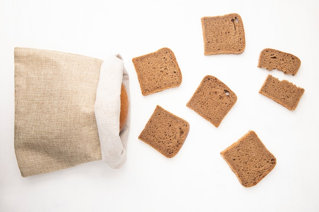 Top view of rye bread slices and sack with bread on white background with copy space