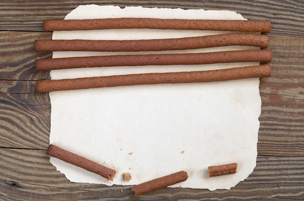 Top view on rye bread sticks on old paper located on wooden background